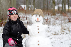 Cute girl with snowman Stock Photo