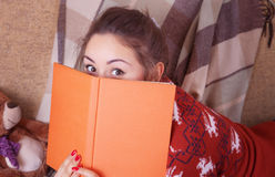 Cute girl on the sofa with a book Royalty Free Stock Photos