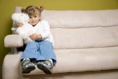 Cute girl with soft teddy bear. On sofa Royalty Free Stock Photo