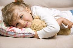 Cute girl with soft teddy bear. On sofa Royalty Free Stock Photos