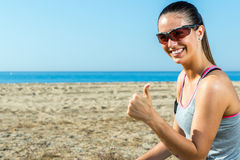 Cute girl in sports wear doing thumbs up outdoors. Royalty Free Stock Photos