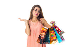 Cute girl spreads her hand and holds the multicolored bags isolated on white background Royalty Free Stock Photos