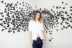 Cute girl standing on a fantastic background with lots of butterflies Stock Image