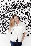 Cute girl standing on a fantastic background with lots of butterflies Stock Photo