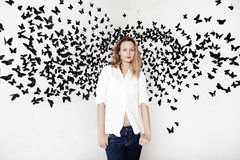 Cute girl standing on a fantastic background with lots of butterflies Royalty Free Stock Images
