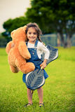 Cute girl standing in the grass holding teddy bear Royalty Free Stock Photo