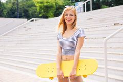 Cute girl standing with skateboard stock photos
