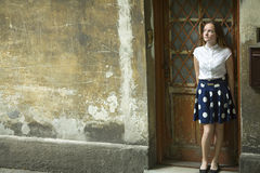 Cute girl stands near the door of the old house. Royalty Free Stock Photo