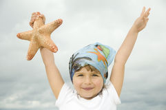 Cute girl with starfish on the beach Stock Photo