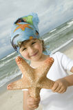Cute girl with starfish on the beach Stock Photos