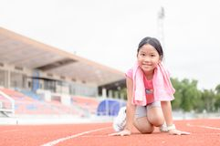 Cute girl in starting position ready for running. Kid athlete about to start a sprint looking at camera with bright sunlight. diet and exercise concept Stock Images