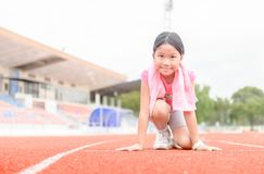 Cute girl in starting position ready for running. Kid athlete about to start a sprint looking at camera with bright sunlight. diet and exercise concept Stock Photo