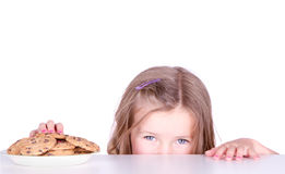 A cute girl steals cookies Stock Images
