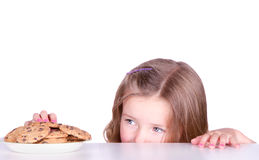A cute girl steals cookies Royalty Free Stock Image
