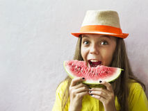 Cute girl in a straw hat with a ripe watermelon. Royalty Free Stock Photo