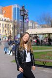 Cute girl strolling in city. Cute girl strolling in city and wearing leather jacket. Concept of spring weather and walking outdoors Royalty Free Stock Photography