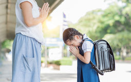 Cute girl student pay respect to her mother. Before going to school.Thai culture royalty free stock photos