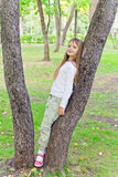 Cute girl in summer sit on tree Royalty Free Stock Photo