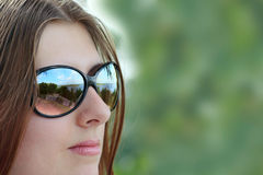 The cute girl in sun glasses. The nice girl in sun glasses removed close up Royalty Free Stock Photo