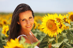 Cute girl with sunflower. Beautiful young woman posing in a field of sunflowers Stock Photo