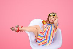 Cute girl in sunglasses with lollipop. Charming trendy little girl in striped dress and sunglasses holding bright lollipop looking at camera smiling on pink Royalty Free Stock Photography