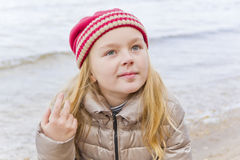 Cute girl in sunlight. Autumn portrait of blond girl on riverside royalty free stock images