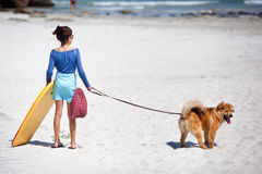 Cute girl with surfboard and dog at the beach Royalty Free Stock Images