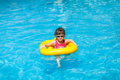 Cute girl swims in a pool in a yellow life preserver Royalty Free Stock Photography