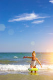 Cute girl in swimsuit bathes on waves in sea. Sunny Mediterranea Stock Photography
