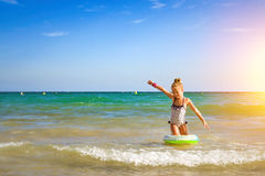 Cute girl in swimsuit bathes on waves in sea. Sunny Mediterranea Royalty Free Stock Photo