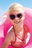 Cute girl in swimsuit playing with an inflatable ring on the seaside Stock Photo
