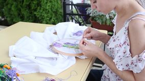 Cute girl at table sewing with needle. needlework, embroidery, hobby, handicraft stock video
