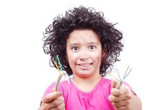 Cute girl is taking electrical wire. A cute girl is taking an electrical wire in hands Royalty Free Stock Photo