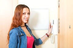 Cute girl talking on the house videophone indoor Royalty Free Stock Image