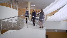 Cute girl talking, standing on a stone staircase in the building. They are dressed in designer dresses, beautifully stock footage