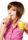 Cute girl with a tea cup biting a pretzel Royalty Free Stock Images