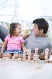 Cute girl teasing father while playing with wooden building blocks at home Stock Photography