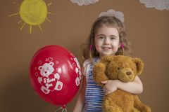 Cute girl with teddy bear holding red balloon, smiling at camera. Royalty Free Stock Photography
