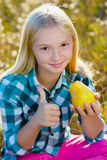 Cute girl or teenager eaten healthy and juicy pear outdoor Stock Photo