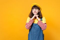 Cute girl teenager in french beret, denim sundress looking aside, holding hands near chin isolated on yellow wall. Background in studio. People sincere emotions royalty free stock photography