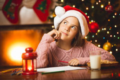 Cute girl thinking of letter to Santa at living room Stock Images