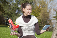 Cute girl thinks about online shop. Concept of online shopping- cute girl thinks what to shop online- with tablet PC and shopping trolley Stock Photography