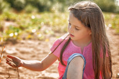 Cute girl thoughtfully playing with sand in park Royalty Free Stock Photos