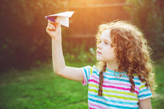 Cute girl throwing paper airplane at summer park. Happy childhoo Royalty Free Stock Images