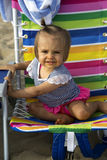 Cute girl toddler in a colorful beach chair Royalty Free Stock Photos
