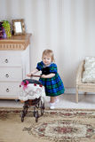Cute girl with toy pram Stock Image