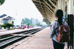 Cute girl in train station waiting to travel. Summer holiday. Royalty Free Stock Images