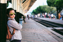 Cute girl in train station waiting to travel. Summer holiday. Stock Photos