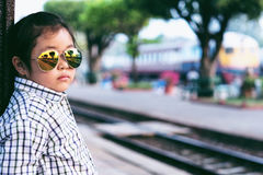Cute girl in train station waiting to travel. Summer holiday Royalty Free Stock Image