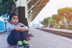 Cute girl in train station waiting to travel. Summer holiday Stock Photo